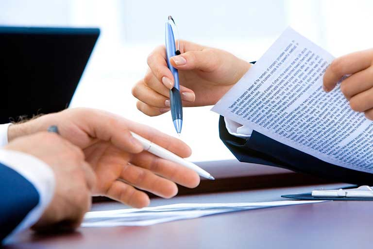Hands signing legal papers